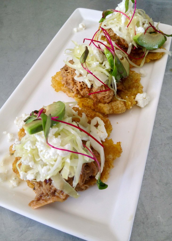 Patacones with pulled pork, avocado, slaw, and cheese