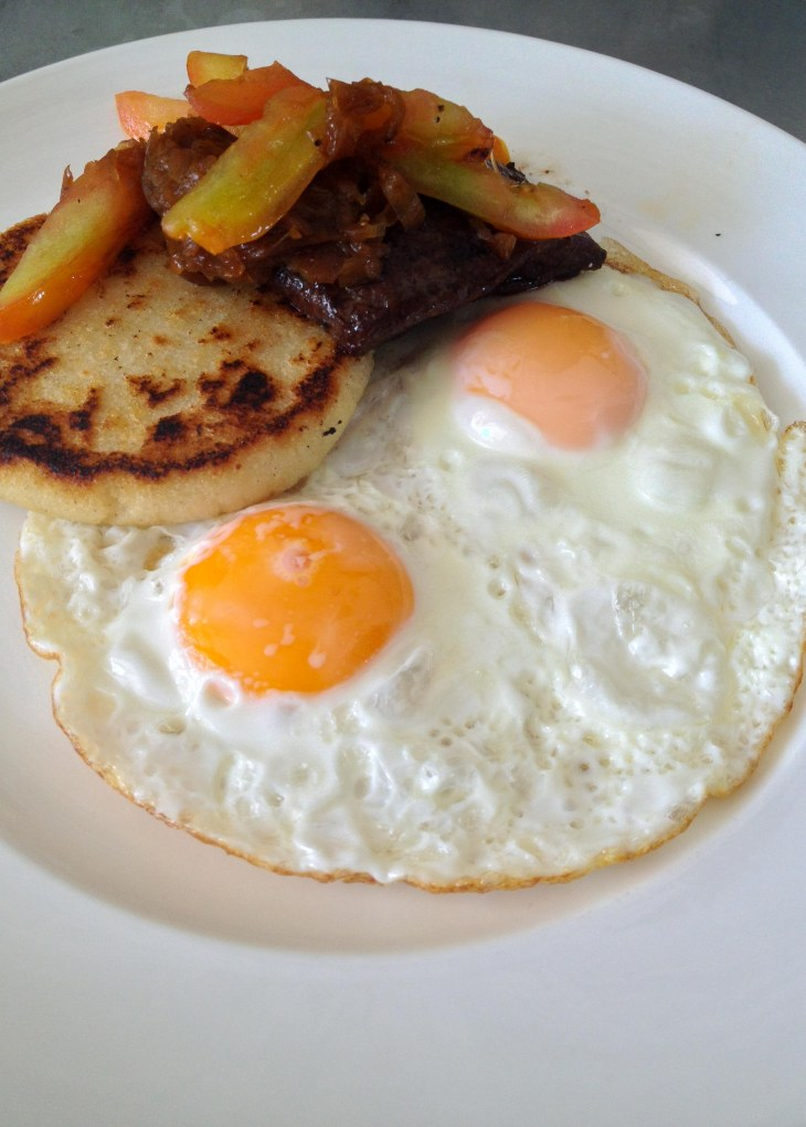 Steak and fried eggs with arepa