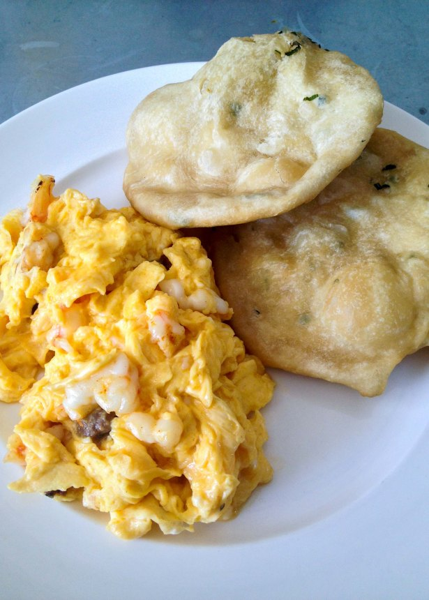 Scrambled eggs with prawns, chorizo, and hojaldre (fried bread)